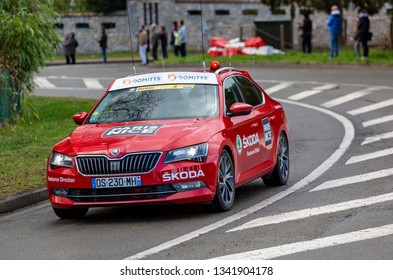 Beulle, France - March 10, 2019: The Red car of organizers driving on Cote de Beulle during the stage 1 of Paris-Nice 2019.