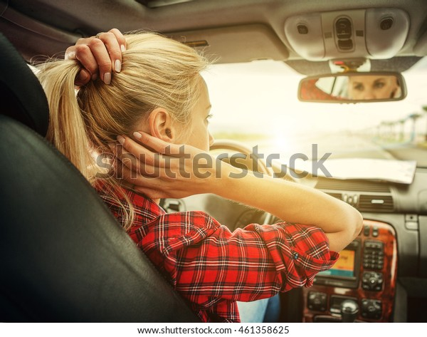 Beutiful blond girl comb her hair with a rearview mirror in car