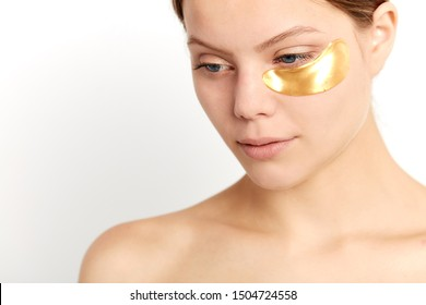 beutiful girl with natural makeup and gold cosmetics collagen patches on fresh facial skin looking down, close up portrait, studio shot