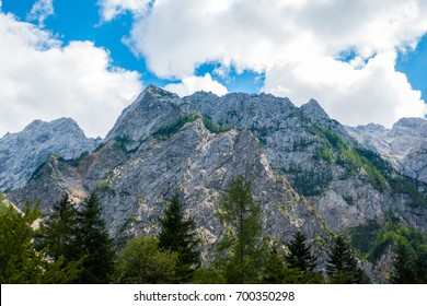 A beutiful landscape in the mountains, clouds above peaks and forest in foreground, European Alps, Logarska valley, Slovenia