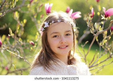 Beutiful little girl with handmade hair wreath on her head smiling looking at camera in the blooming spring garden with magnolia blossom on background, close-up