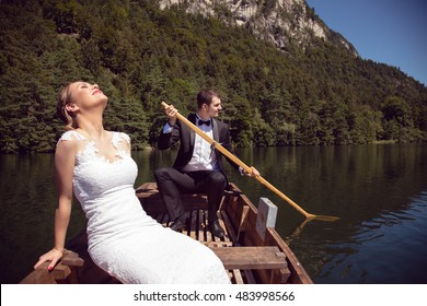Beutiful man and woman just married sailing in a boat on the clear lake