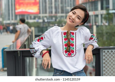 Beutiful smiling chinese young woman wearing traditional ukrainian clothes posing in center of Beijing city, China.
