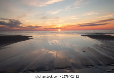 Beutiful sunset and formations in the sand made by the water of the ocean
