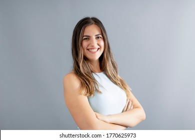 Beutiful Turkish young woman crossed arm posing in confident mood and smiling, grey background studio shot.