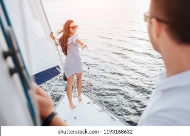 Beutiful and well-built model stands on bow of yacht and holds on tube. She looks behind herself at boyfriend. Brunette try to reaches him with hand and smiles. Young man stands and looks.