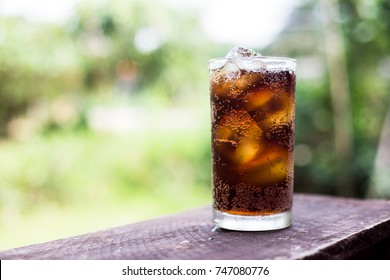 Beverage from cola in glass with ice on the wood,beverage in summer is sparkling water