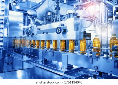 Beverage factory, Conveyor belt with juice in bottles, Industrial Interior in blue color, food and drink production line process.