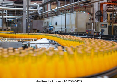 Beverage factory interior. Conveyor flowing with bottles for juice or water.