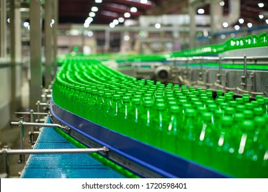 Beverage factory interior. Conveyor flowing with bottles for juice green or water.