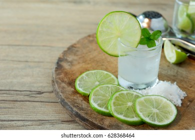 Beverage made from lemon soda and pepermint maybe fill vodka for cocktail served with salt and lemon slices on wood Chopping board