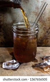 Beverage In Mason Jar With Ice Cubes and Reusable Glass Straw