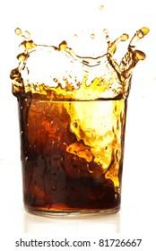 beverage splashing into glass on a white background