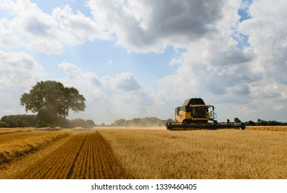 BEVERLEY, UK - AUGUST 10, 2018: Modern machinery harvests a field of oats on a bright sunny morning in summer on August 10, 2018 in Beverley, Yorkshire, UK.