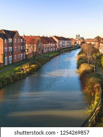 BEVERLEY, UK - DECEMBER 09, 2011: The beck (canal) with fishermen and lined by town houses and the ancient minter on horizon on bright autumn morning on December 09, 2011 in Beverley, Yorkshire, UK.