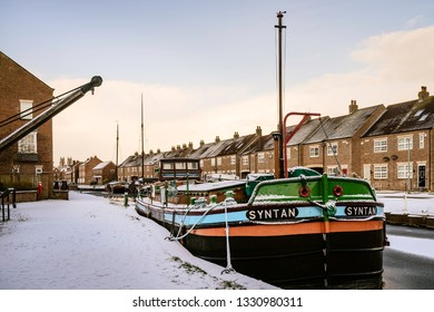 BEVERLEY, UK - JANUARY 02, 2019: Vintage barges moored along the frozen beck (canal) and covered in snow flanked by town houses on January 02, 2019 in Beverley, Yorkshire, UK.