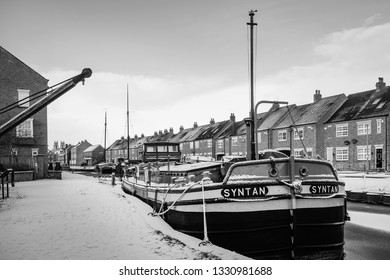 BEVERLEY, UK - JANUARY 02. 2019: Vintage barges moored along the frozen beck (canal) and covered in snow flanked by town houses on January 02, 2019 in Beverley, Yorkshire, UK.