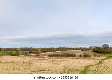 Beverley, Yorkshire, UK. Agricultural landscape and parklands with trees and ancient minster on horizon and railway train in spring in Beverley, Yorkshire, UK.