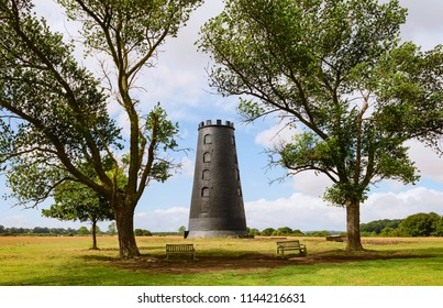 Beverley, Yorkshire, UK. The Black Mill, popular landmard, flanked by tress and cattle grazing on a bright, sunny, summer morning, Beverley, Yorkshire, UK.