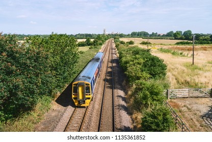 Beverley, Yorkshire, UK. Railway train flanked by agricultural fields and trees and heading towards ancient minster on horizon, Beverley, Yorkshire, UK.