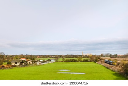 Beverley, Yorkshire, UK. Rural scene with farmhouses, train, fields, and ancient minster on horizxon on bright spring morning in Beverley, Yorkshire, UK.