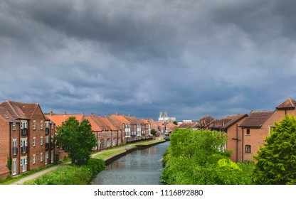 Beverley, Yorkshire, UK. Storm clouds gather over the ancient minster, town houses, and the beck in spring, Beverley, Yorkshire, UK.