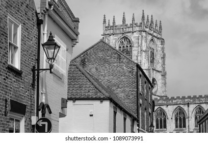 Beverley, Yorkshire, UK. View of St Mary's church and belfry as viewed from Ladygate flanked by brick buildings against blue sky in spring in Beverley, Yorkshire, UK.