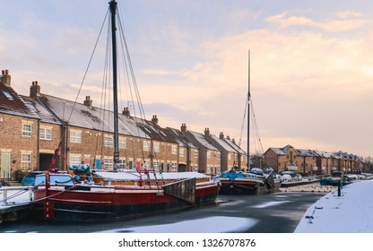 Beverley, Yorkshire, UK. Vintage barges moored along the frozen beck (canal) and covered in snow flanked by town houses on a cold winter morning in Beverley, Yorkshire, UK.