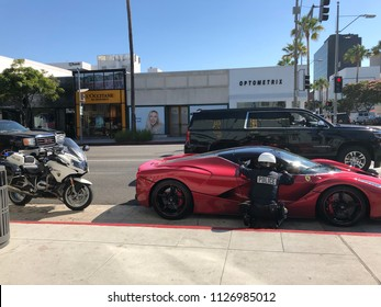 Beverly Hills, CA: June 3, 2018: A Beverly Hills Police Officer talking with a driver in an exotic vehicle.  Beverly Hills is an upscale city in Southern California.
