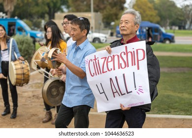 "BEVERLY HILLS, CALIFORNIA - MARCH 12, 2018: A protester with the Korean Resource Center holds a sign that reads, ""Citizenship 4 All!"" at the Defend Dreamers Rally hosted by Coalition for Humane Immigr"