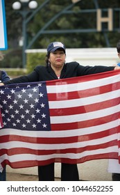 BEVERLY HILLS, CALIFORNIA - MARCH 12, 2018: A protester holds the USA Flag at the Defend Dreamers Rally hosted by Coalition for Humane Immigrant Rights (CHIRLA).