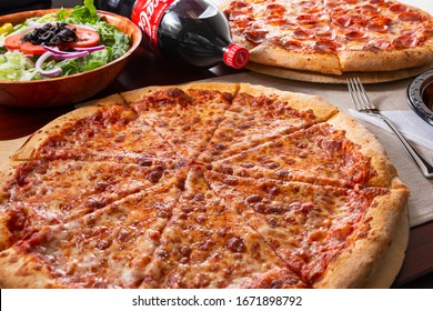 Beverly Hills, California/United States - 02/23/2020: A food presentation of two pizza pies, a salad, and a bottle of Coca-Cola soda, in a restaurant or kitchen setting.
