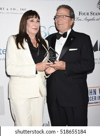 """BEVERLY HILLS - NOV 19:  Anjelica Huston and Patrick Wayne arrives to the Associates For Breast, Prostate Cancer Studies """"Talk Of The Town"""" Gala on November 19, 2016 in Los Angeles, CA"""