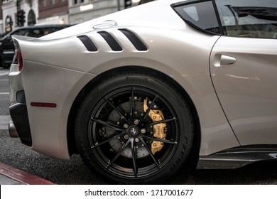 Beverly Hills, Year 2016: White Ferrari F12 TDF parked on Wilshire Blvd, Beverly hills. Rear, air intake, spoiler, fender, exhaust pipe, rim and wheel, brake disc and caliper, bumper, door and window.