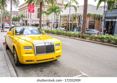 BEVERLY HILLS,CA - DECEMBER 18, 2013: yellow rolls royce at Rodeo Drive,Beverly Hills CA. Rodeo Drive is a shopping district famous for designer label and  couture fashion