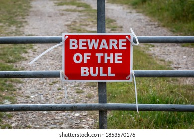 A Beware of the Bull warning sign on a gate in the countryside