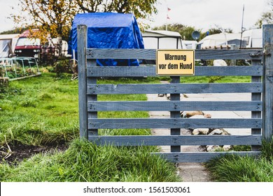 """""""Beware of Dog"""" sign in German language on blue wooden fence in front of trailer park"""