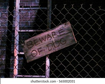 A Beware of the Dog sign on a wire fence