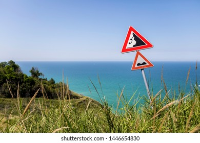 Beware of falling rocks! Quirky scene with a information sign on the steep bank in front of a beautiful mediterranean scenery.
