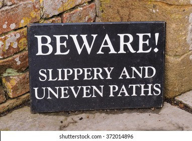 """Beware !, Slippery and Uneven Paths"" Sign in the Rural Village of Tintinhull in Somerset, England, UK"