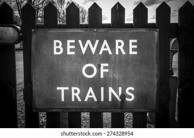 Beware of Trains sign on a wooden fence.