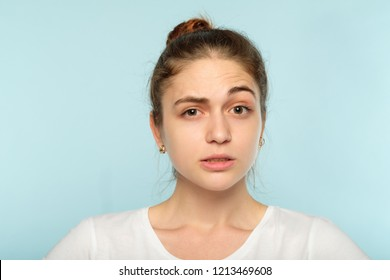 bewildered dubious distrustful girl with raised eyebrow. young beautiful woman with a hair bun on blue background. emotional facial expression.