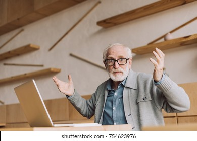 bewildered senior man with laptop sitting in cafe and looking at camera with raised hands