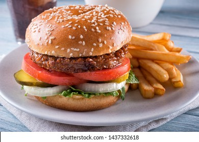 A beyond delicious plant based non meat burger with lettuce, onion, pickle, tomato and french fries.