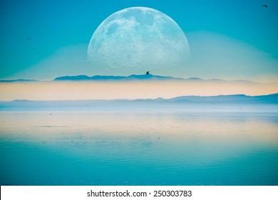 Beyond the Horizon. Fantasy Landscape with Large Moon on the Horizontal, Mountains and the Calm Sea.