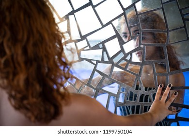 Beyond my reflection! Young girl looking into mirror of reflective mosaic wall, with pensive, contemplative look.