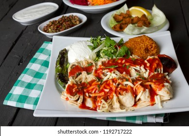 Beyti sarma or adana kebab rolled in lavash bread and grated cheese, tomato sauce on top serving with cig kofte, salad and yogurt. Rustic black wood background.