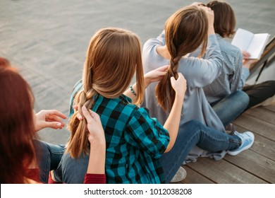 Bff support friendship care. Girls plait each other hair. Teamwork concept