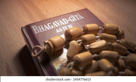Bhagavad Gita and rosary lying on a wooden table. - Shutterstock ID 1454776613
