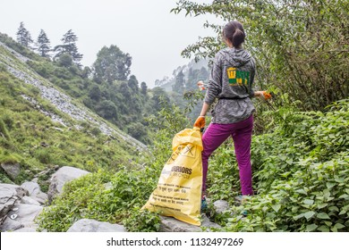 Bhagsu, Himachal Pradesh / India - July 12 2018 : A girl from the NGO Waste Warriors is busy cleaning up trash around Bhagsu waterfall on a cool summer day in the Himalayas.